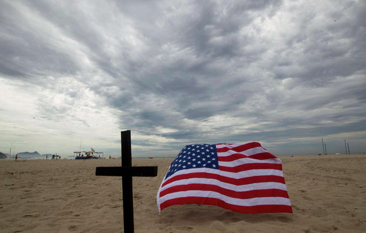 A cross and a U.S. flag are set at the Copacabana Beach in Rio de Janeiro, in memory of the school shooting victims in Newtown, Conn., Saturday, Dec. 15, 2012. (AP Photo/Silvia Izquierdo)