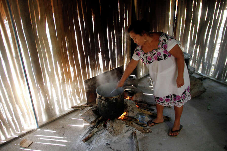 Donaciana Cupul cooks in her home, a traditional stucture, in the Mayan community of Hidalgo in Yucatan state, Mexico Friday, Dec. 14, 2012. Mexico's 800,000 Mayas are not the sinister, secretive, apocalypse-obsessed race they've been made out to be. In their heartland on Mexico's Yucatan peninsula, Mayas continue their daily lives. Many still live simply in thatched, oval, mud-and-stick houses designed mostly for natural air-conditioning against the oppressive heat of the Yucatan, where they plant corn, harvest oranges and raise pigs. (AP Photo/Israel Leal) / AP