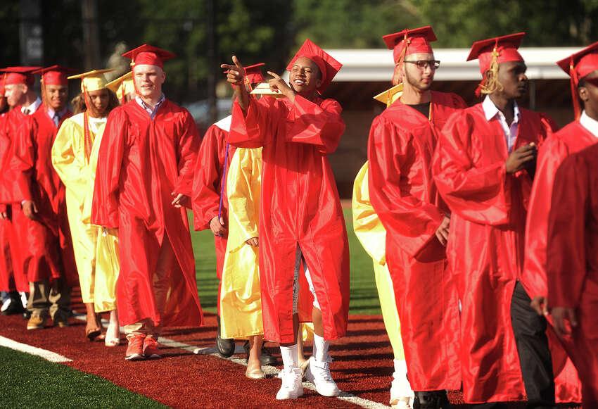 Deshawn Sawyer acknowledges his supporters as he walks in with fellow graduates to the Stratford High School graduation at Penders Field in Stratford, Conn. on Wednesday, June 15, 2016.