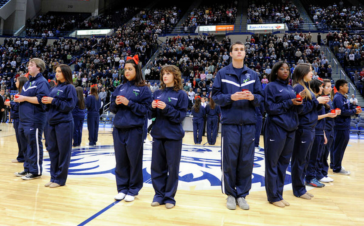 Members of the Connecticut's band, cheer, dance and basketball teams participate in a service in memory of those killed in Friday's school shooting in Newtown, Conn., before an NCAA college basketball game against Oakland in Hartford, Conn., Wednesday, Dec. 19, 2012. (AP Photo/Fred Beckham)
