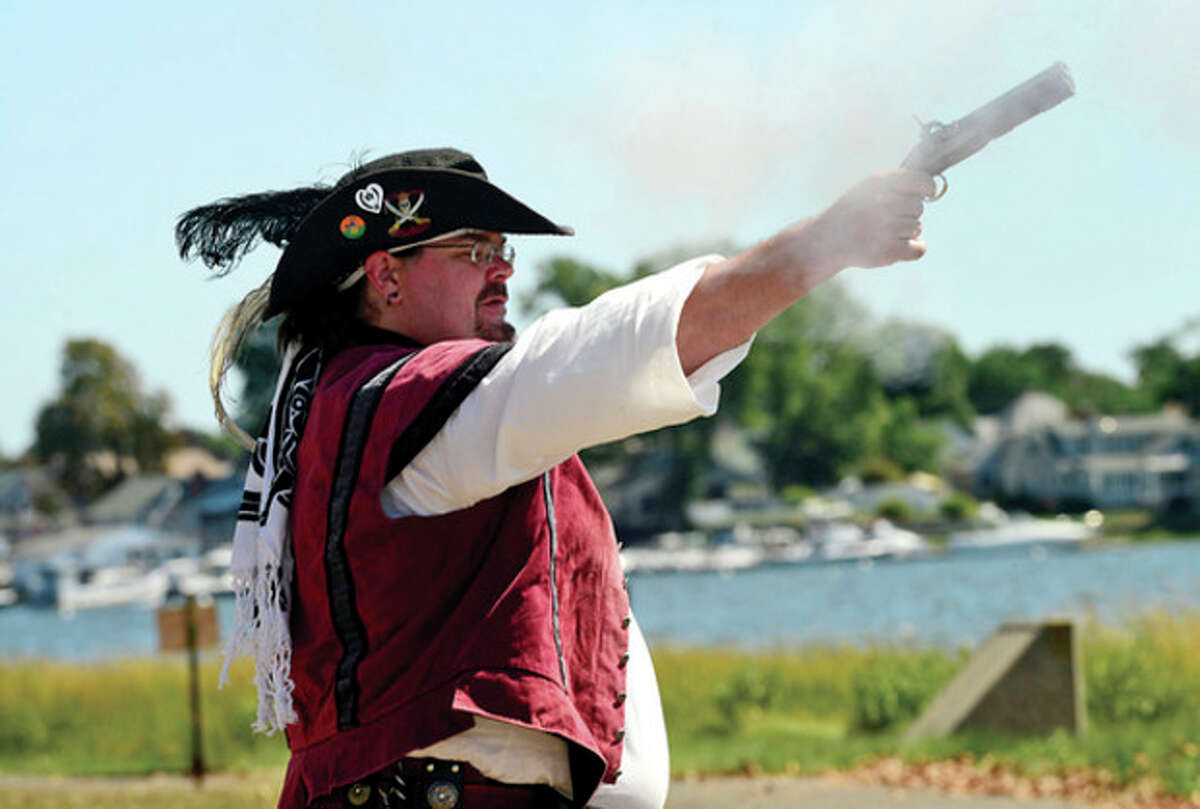 At right, 2-year-old Savanna Eliasson enjoys visiting Pirate Cove during the 36th annual Norwalk Oyster Festival Saturday. Below, a pirate performs a flintlock demonstration during the Norwalk Oyster Festival.
