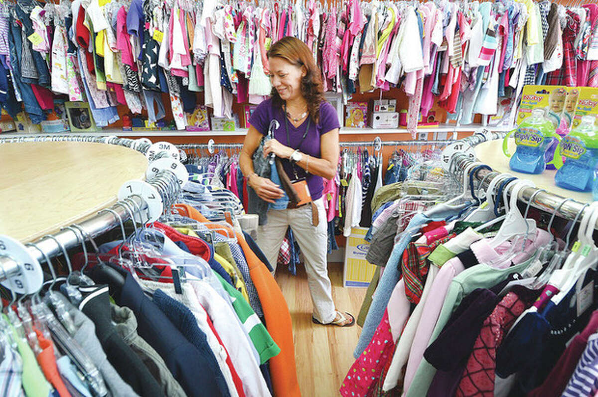 Hour Photo/Alex von Kleydorff Marsha Dunn finds some room on the racks for more clothes at Kid Around Resale.