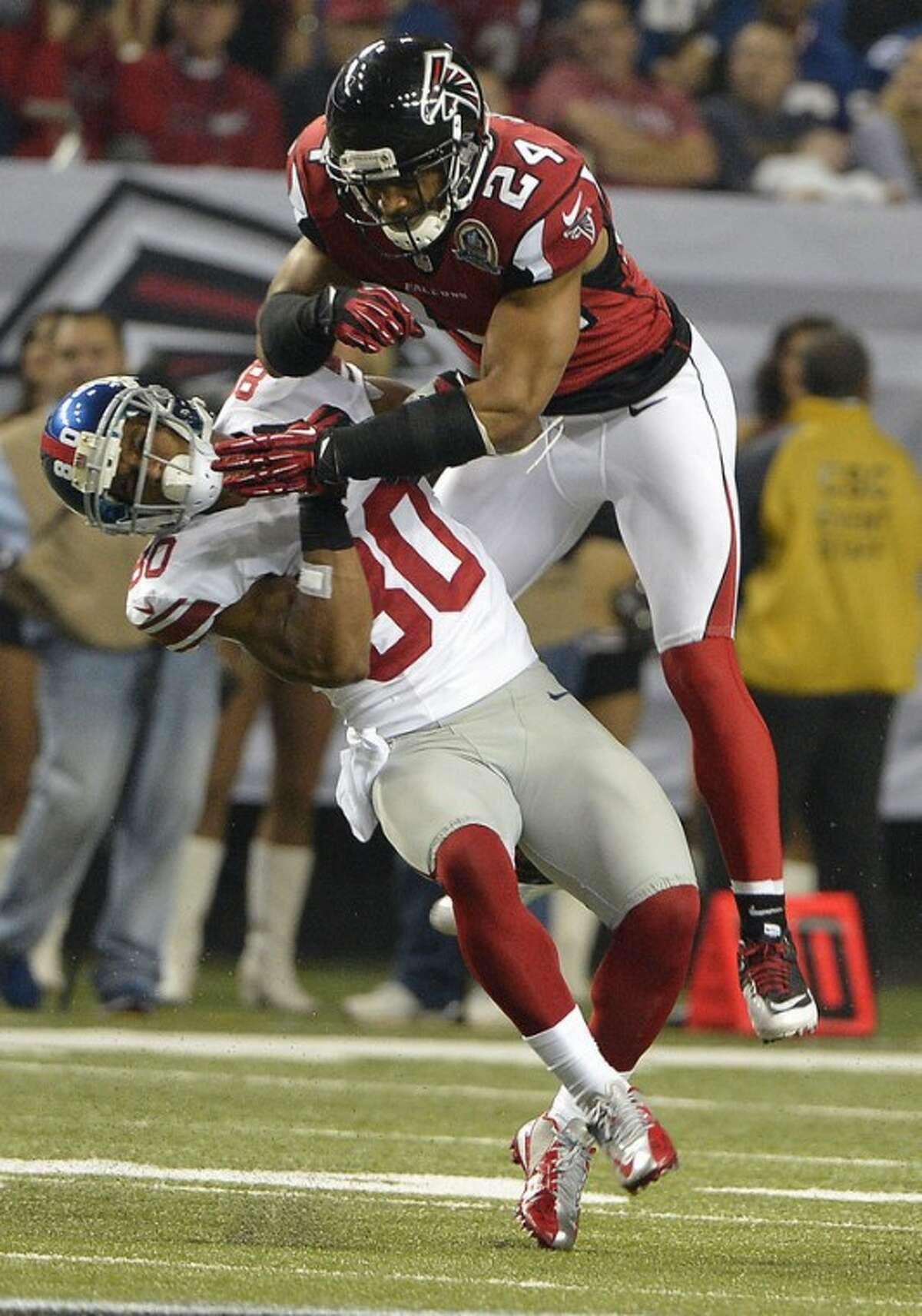 Atlanta Falcons strong safety Chris Hope (24) hits New York Giants wide receiver Victor Cruz (80) during the second half of an NFL football game on Sunday, Dec. 16, 2012, in Atlanta. (AP Photo/Rich Addicks)