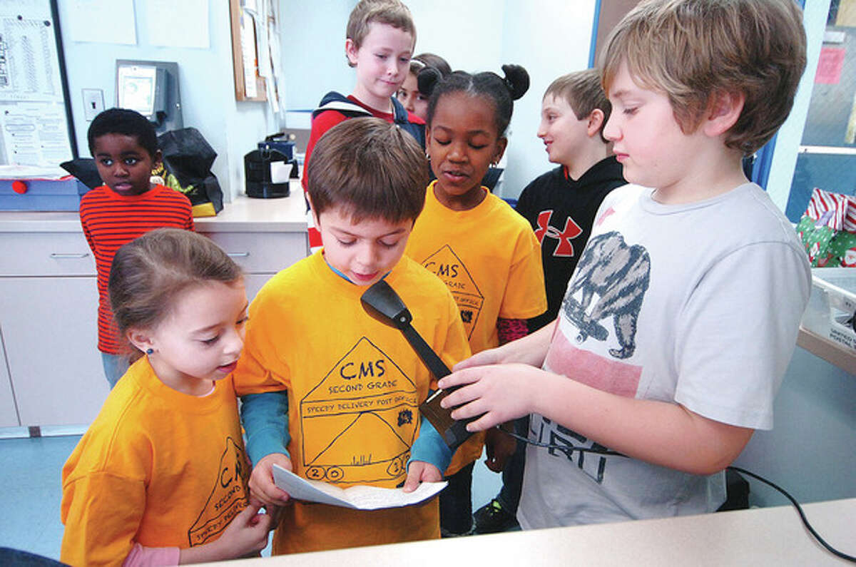 Hour Photo/Alex von Kleydorff. Ryan Whitney holds the schools public address micropone for Christian Atunes while Jeni von Bartheld and Amya James wait to announce the post office is open at Columbus Magnet School