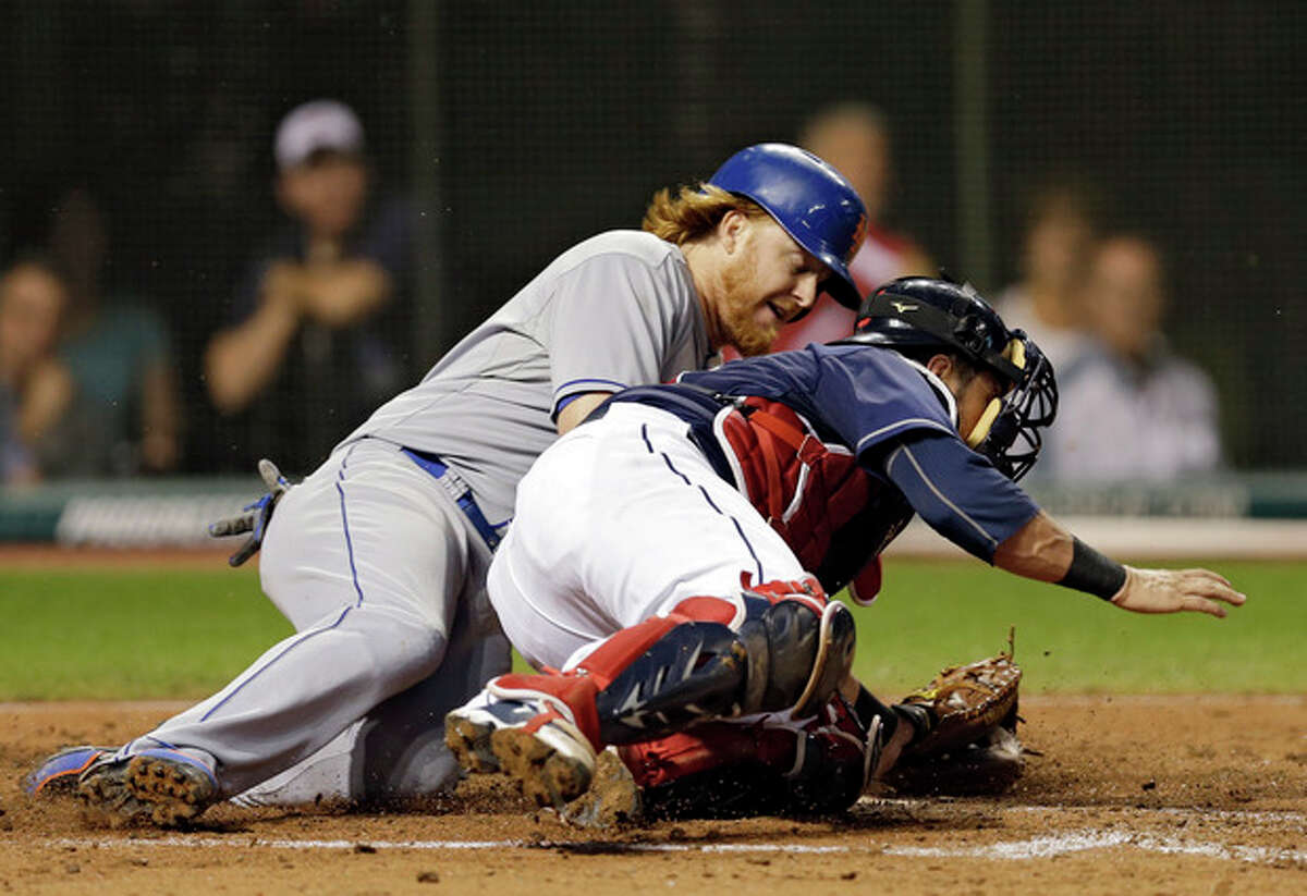 New York Mets' Justin Turner, left, slides home on Cleveland Indians catcher Yan Gomes to score on a single by Juan Lagares in the sixth inning of a baseball game Saturday, Sept. 7, 2013, in Cleveland. (AP Photo/Mark Duncan)