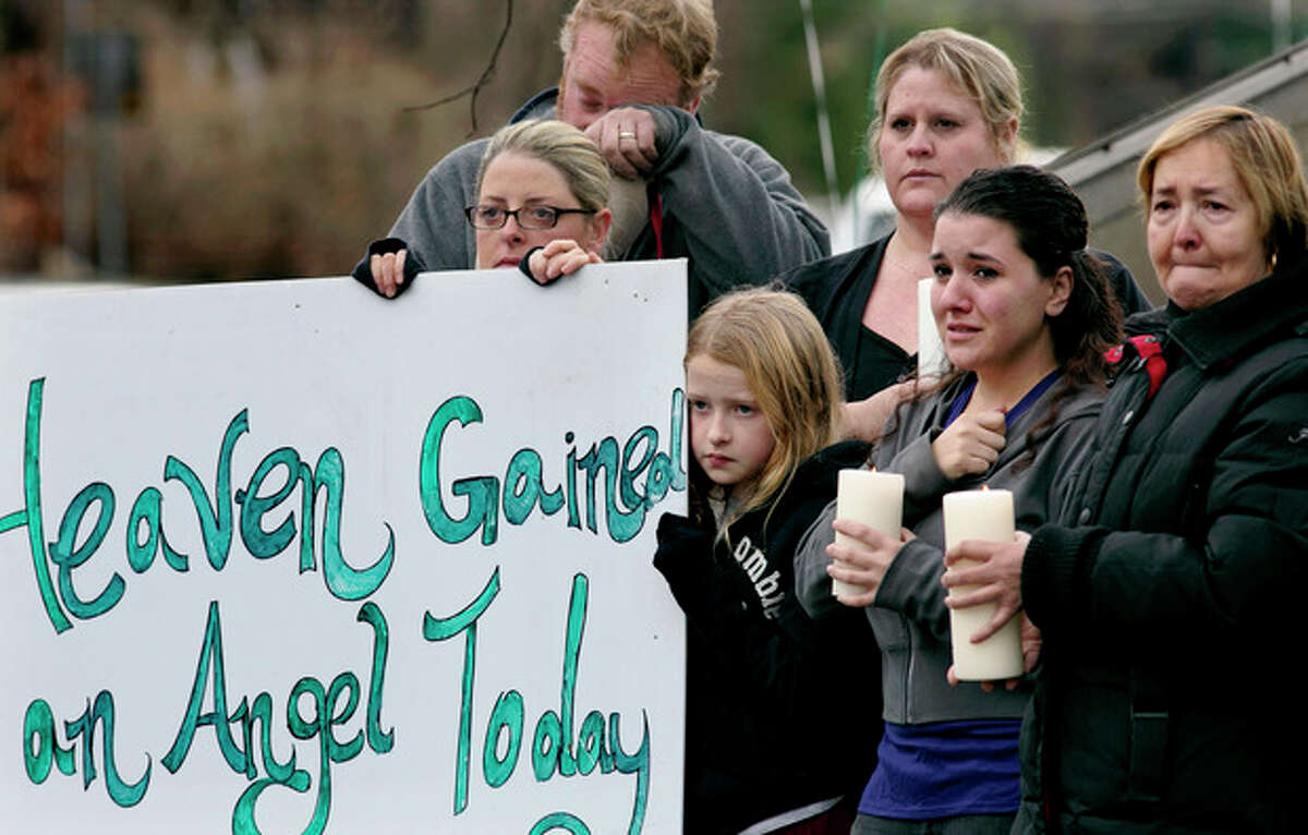 Tom Doyle, back left, standing with family and co-workers, wipes his face as the funeral procession for 6-year-old James Mattioli, who died in the Sandy Hook Elementary School shootings, approaches the St. John's Cemetery Tuesday, Dec. 18, 2012, in Darien, Conn. Center are his wife Debbie and daughter Emily, 10. Adam Lanza opened fire at the Sandy Hook Elementary School in Newtown on Friday, killing 26 people, including 20 children. (AP Photo/Craig Ruttle)