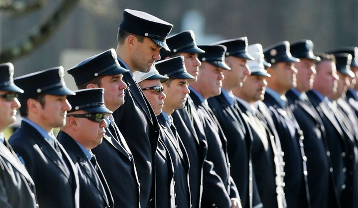 Firefighters line up outside the funeral for school shooting victim Daniel Gerard Barden at St. Rose of Lima Catholic Church in Newtown, Conn., Wednesday, Dec. 19, 2012. According to firefighters, Daniel wanted to be a firefighter when he grew up and they honored him at the service. Gunman Adam Lanza opened fire killing 26 people, including 20 children, at Sandy Hook Elementary School in Newtown before killing himself on Friday. (AP Photo/Charles Krupa)