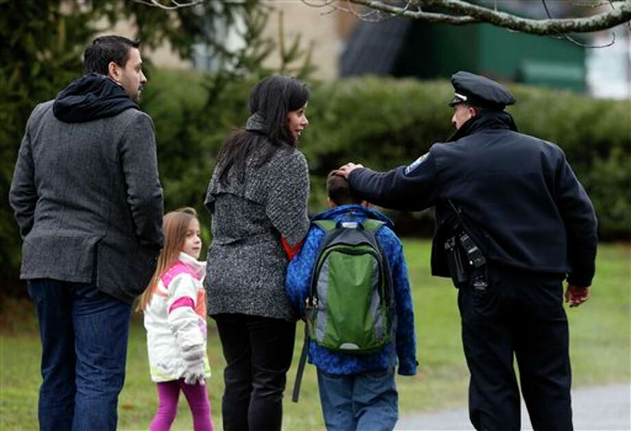 Easton police officer J. Sollazzo greets a returning student as he is walked into Hawley School in Newtown, Conn., Tuesday, Dec. 18, 2012. Classes resumed Tuesday for Newtown, schools except those at Sandy Hook, following Friday's mass shooting at the Sandy Hook Elementary School. Buses ferrying students to schools were festooned with large green and white ribbons on the front grills, the colors of Sandy Hook. At Newtown High School, students in sweatshirts and jackets, many wearing headphones, betrayed mixed emotions. (AP Photo/Jason DeCrow) / FR103966 AP