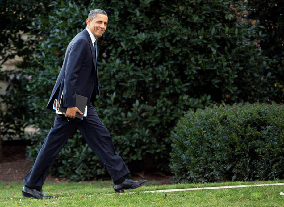 President Barack Obama looks to the media as he walks to the Oval Office of the White House as he returns from greeting members of the staff, Tuesday, Dec. 18, 2012, in Washington. (AP Photo/Carolyn Kaster) / AP