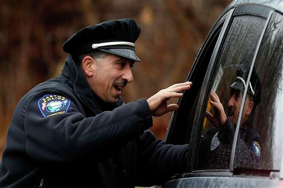 Easton police officer J. Sollazzo waves to a returning student as a car pulls into Hawley School, Tuesday, Dec. 18, 2012, in Newtown, Conn. Classes resume Tuesday for Newtown schools except those at Sandy Hook. Buses ferrying students to schools were festooned with large green and white ribbons on the front grills, the colors of Sandy Hook. At Newtown High School, students in sweatshirts and jackets, many wearing headphones, betrayed mixed emotions. Adam Lanza walked into Sandy Hook Elementary School in Newtown, Friday and opened fire, killing 26 people, including 20 children, before killing himself.(AP Photo/Jason DeCrow) / FR103966 AP