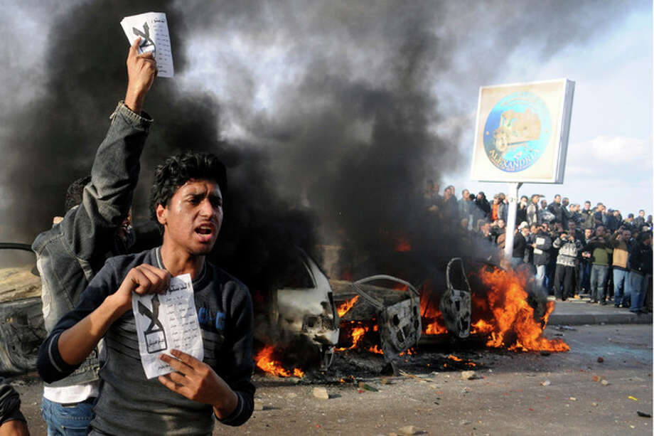 "FILE - In this Friday, Dec. 14, 2012 file photo, opponents of Egyptian President Mohammed Morsi hold pamphlets urging a ""no vote"" on a constitutional referendum as cars burn during clashes between supporters and opponents of President Mohammed Morsi in Alexandria, Egypt. This Mediterranean city with a cosmopolitan heritage, now an Islamist stronghold, is often seen as a predictor of Egypt's trends. So a ferocious battle between sword-wielding Islamists and rock-throwing opponents outside a revered mosque last weekend could be a sign of the volatile direction the country's crisis is taking: Islamists are threatening to take up arms, and young, secular activists are growing bolder in rebelling against their domination. (AP Photo, File) / AP"