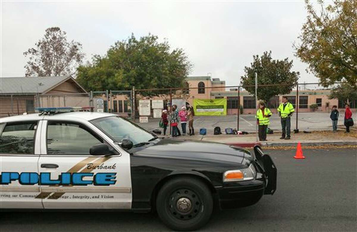 Burbank Police patrol the area as school children and volunteer parents wait outside for the opening of Theodore Roosevelt School in Burbank, Calif., Monday, Dec. 17, 2012. Teachers, parents and students are making an anxious return to school this week after a gunman stormed into Sandy Hook Elementary School in Newtown, Conn., on Friday, shooting to death 26 people before killing himself. (AP Photo/Damian Dovarganes)