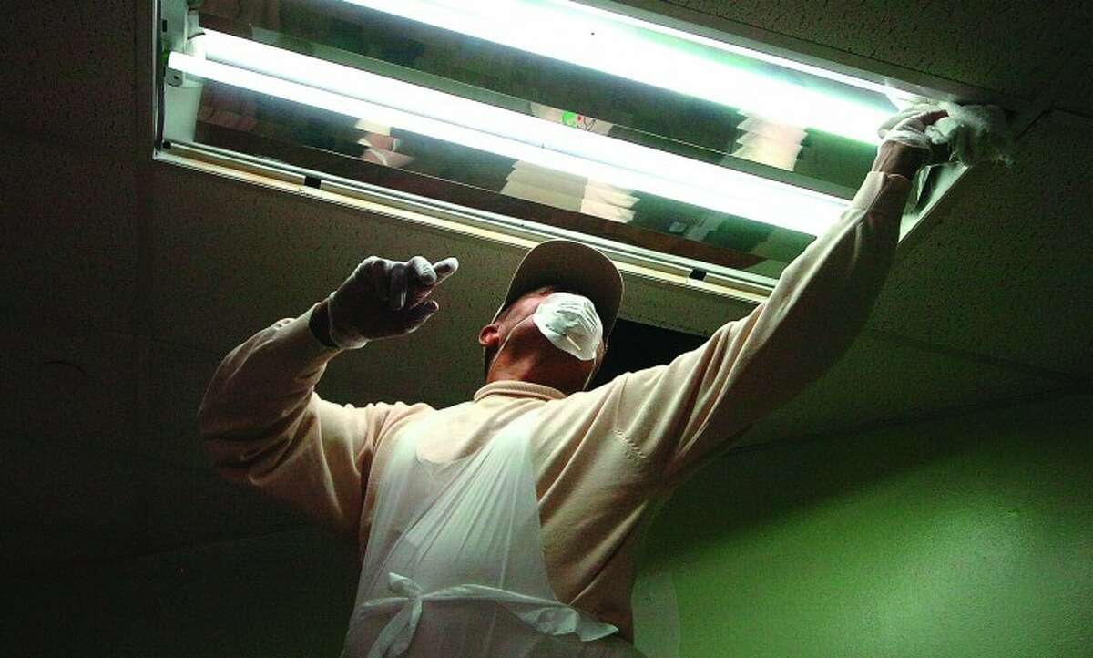 Hour Photo/Alex von Kleydorff. Marbin Barnhona helps by cleaning a new light fixture in the Community Room of the open Door Shelter during a makeover.