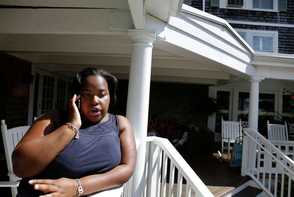 In this Saturday, Aug. 10, 2013 photo White House travel office director Ashley Tate-Gilmore speaks on a cell phone at the entrance to the Vineyard Square Hotel, in Edgartown, Mass., on the island of Martha's Vineyard. A large entourage of staff and press travel with President Barack Obama wherever he goes, even on an island getaway to Martha?'s Vineyard. And their behind-the-scenes movements are juggled by Tate-Gilmore who has been with him since his Chicago days. Tate-Gilmore heads the White House Travel Office. It?'s a five-person operation that handles precise logistics behind every presidential trip. (AP Photo/Steven Senne)