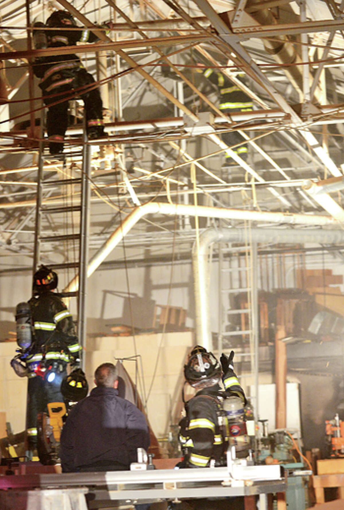 A roof fire briefly reignited on the roof of a cabinet shop at 302 Wilson Ave Wednesday aving. Hour photo / Erik Trautmann