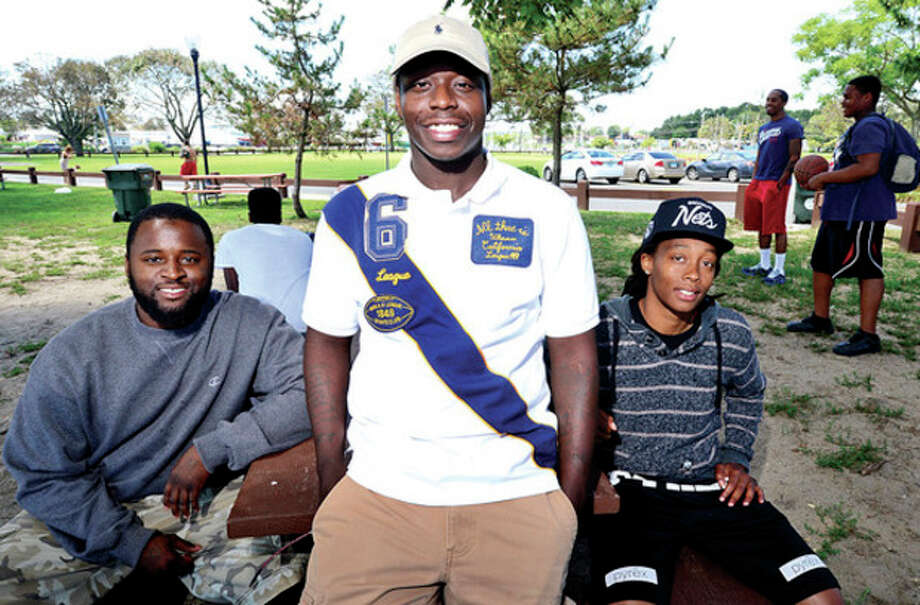 Hour photo / Erik TrautmannNorwalk Housing Authority volunteer Dajuan Wiggins flanked by fellow NHA counselors, Anthony Wilson and April Jackson during a barbeque for the 20 West Avenue Learning Center at Calf Pasture Beach Thursday. / (C)2013, The Hour Newspapers, all rights reserved