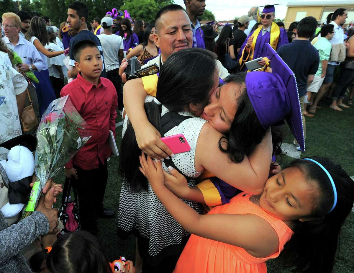 Katherine Martinez is hugged by her family following the Westhill High School Class of 2016 commencement at the school in Stamford, Conn., on Wednesday, June 15, 2016. From left are Martinez brother Angel D. Uchupailla, 12, her father Angel Uchupailla, mother Adelina Uchupailla and sister Jocelyn Uchupailla, 7.