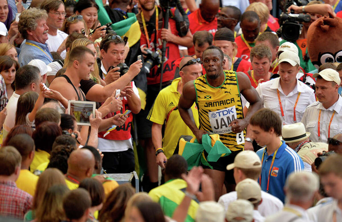 Jamaica's Usain Bolt is surrounded by spectators after he won gold in the men's 4x100-meter relay final at the World Athletics Championships in the Luzhniki stadium in Moscow, Russia, Sunday, Aug. 18, 2013. (AP Photo/Martin Meissner)