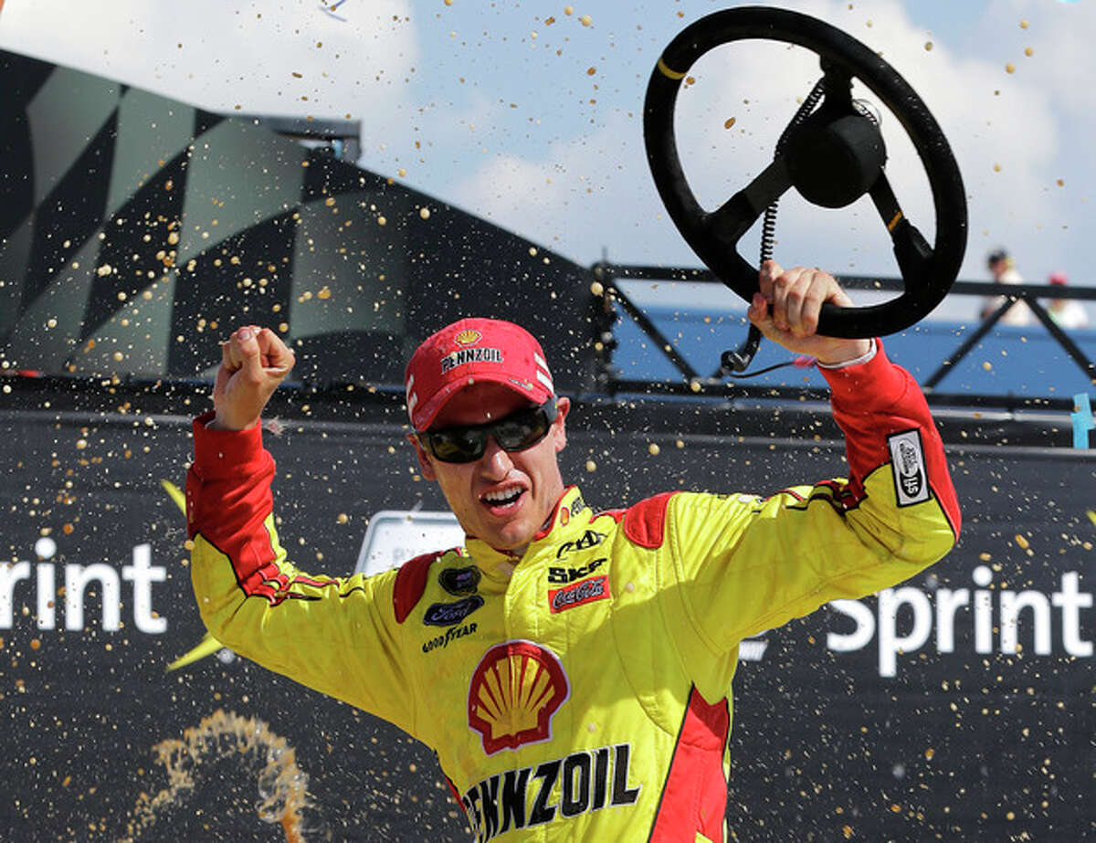 Joey Logano celebrates after winning the NASCAR Sprint Cup series Pure Michigan 400 auto race at Michigan International Speedway in Brooklyn, Mich., Sunday, Aug. 18, 2013. (AP Photo/Paul Sancya)