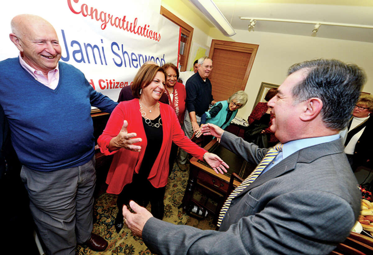 Jami Sherwood is surprised with being named City of Stamford Citizen of the Year as she is greetd by Stamford Mayor Michael Pavia and past Citizen of the Year Al Sanseverino during a morning reception at Redniss and Mead Thursday. Hour photo / Erik Trautmann