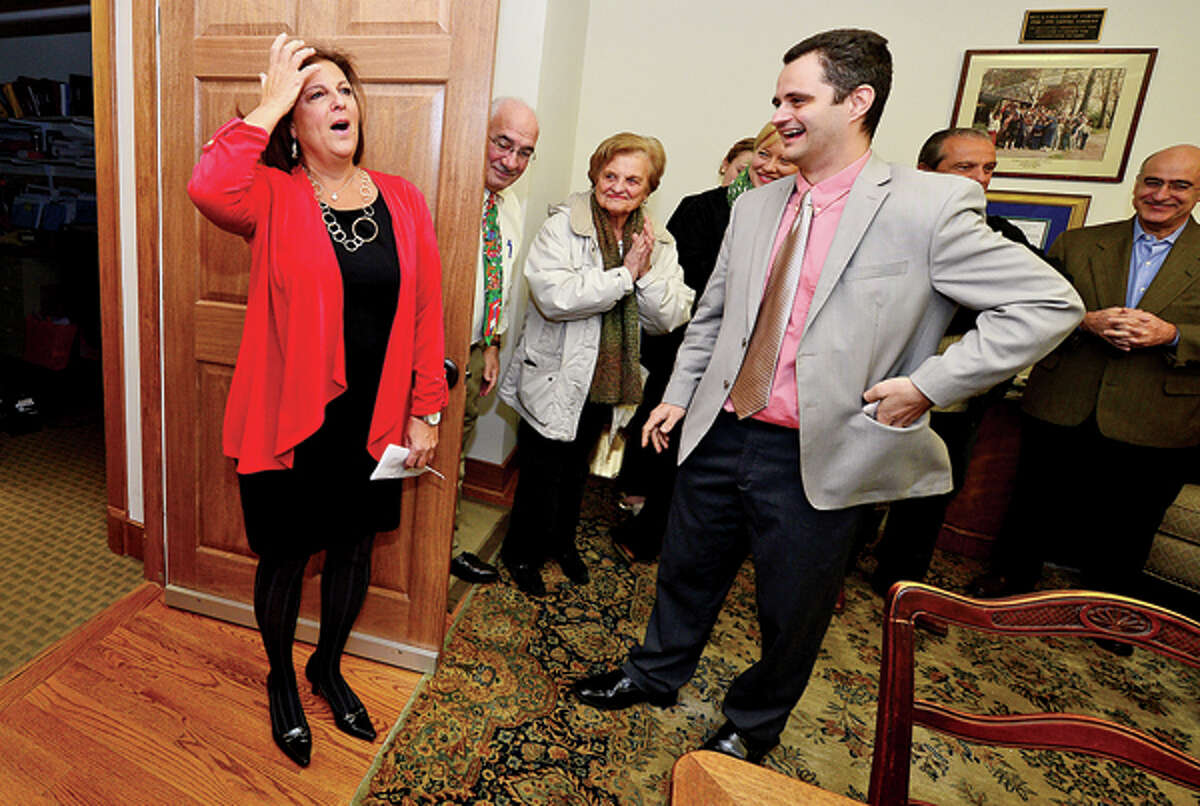 Jami Sherwood is surprised with being named City of Stamford Citizen of the Year when greeted with friends and co workers including Naiden Stoyanov during a morning reception at Redniss and Mead Thursday. Hour photo / Erik Trautmann