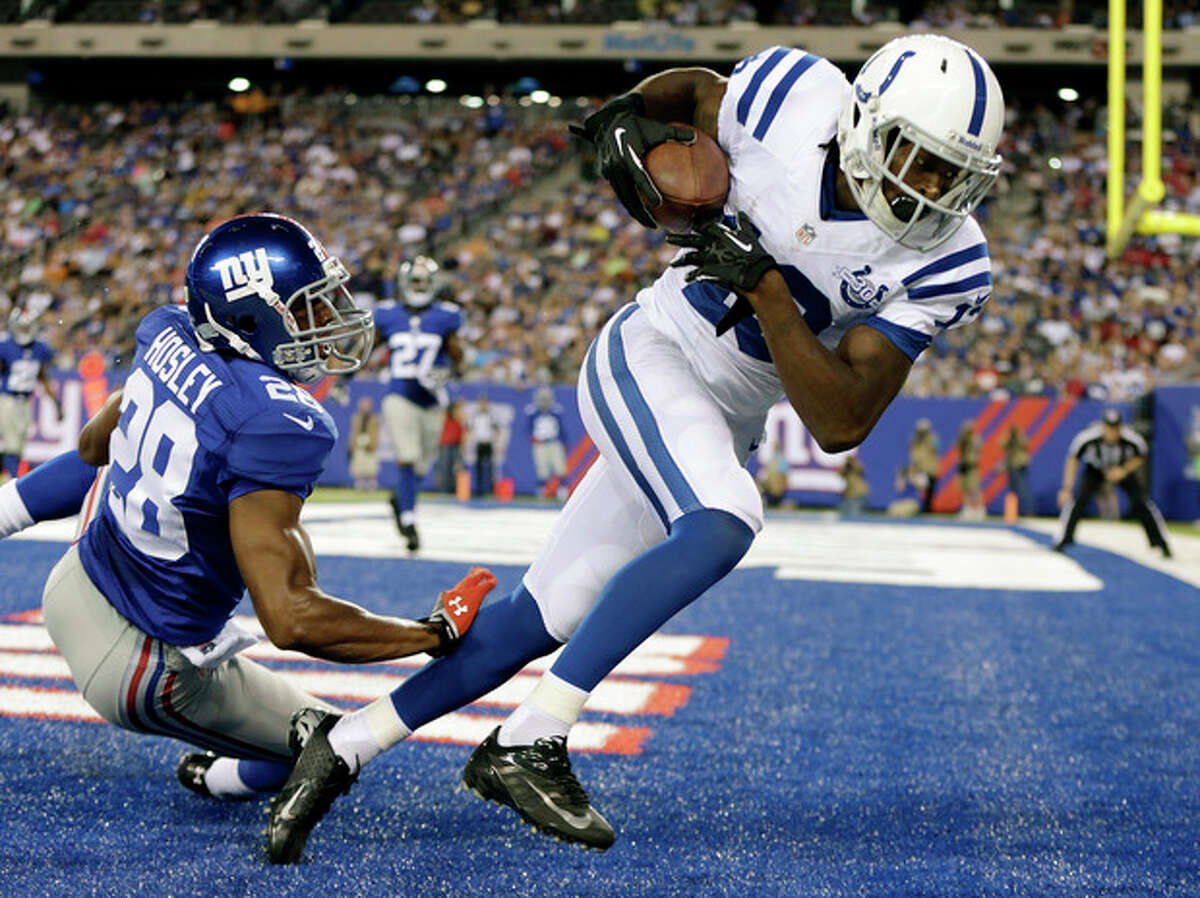 Indianapolis Colts wide receiver T.Y. Hilton (13) catches a pass for a touchdown in front of New York Giants' Jayron Hosley (28) during the first half of an NFL preseason football game Sunday, Aug. 18, 2013, in East Rutherford, N.J. (AP Photo/Kathy Willens)