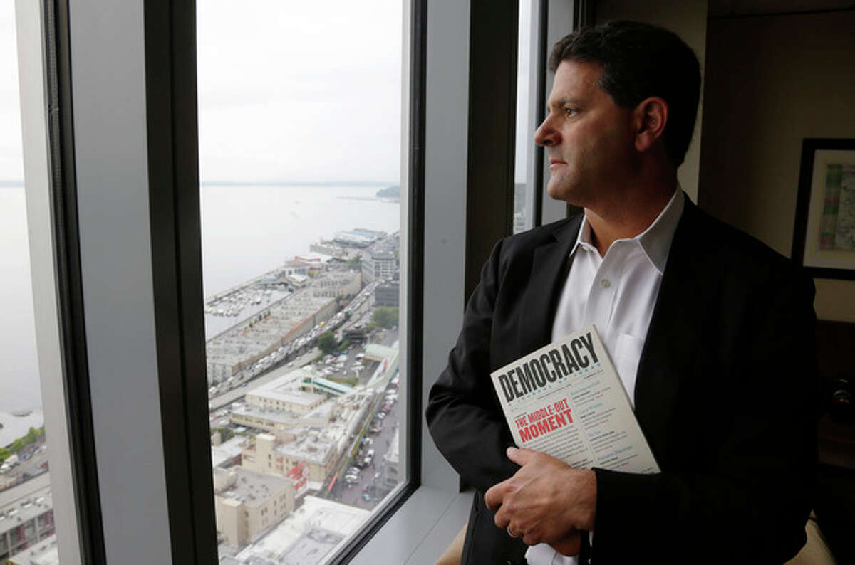 In this Aug. 2, 2013 photo, Venture capitalist Nick Hanauer poses for a photo by the window of his office in downtown Seattle. Washington state already has the nation?'s highest state minimum wage at $9.19 an hour, and Hanauer endorses calls to raise it, because he feels putting money in the hands of regular consumers could reduce the drop in demand for goods that he says has hurst our economy. Hanauer is holding a copy of