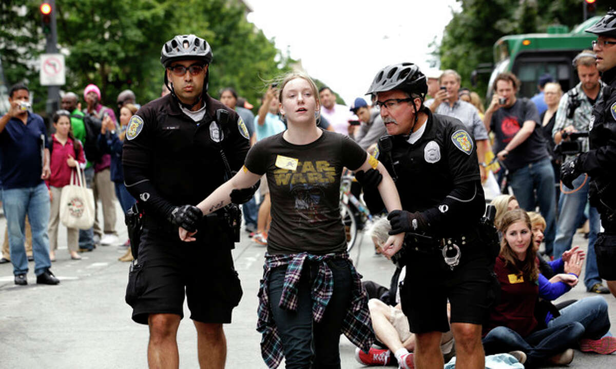 FILE -- In this Aug. 1, 2013 file photo, Seattle police officers take Caroline Durocher, center, into custody after Durocher sat in a downtown intersection during a protest by fast food workers and supporters in Seattle. Durocher works at a Subway sandwich shop. Washington already has the nation?'s highest state minimum wage at $9.19 an hour. Now, there?'s a push in Seattle, at least, to make it $15. That would mean fast food workers, retail clerks, baristas and other minimum wage workers would get what protesters demanded when they shut down a handful of city restaurants in May and others demonstrated nationwide in July. (AP Photo/Elaine Thompson, File)