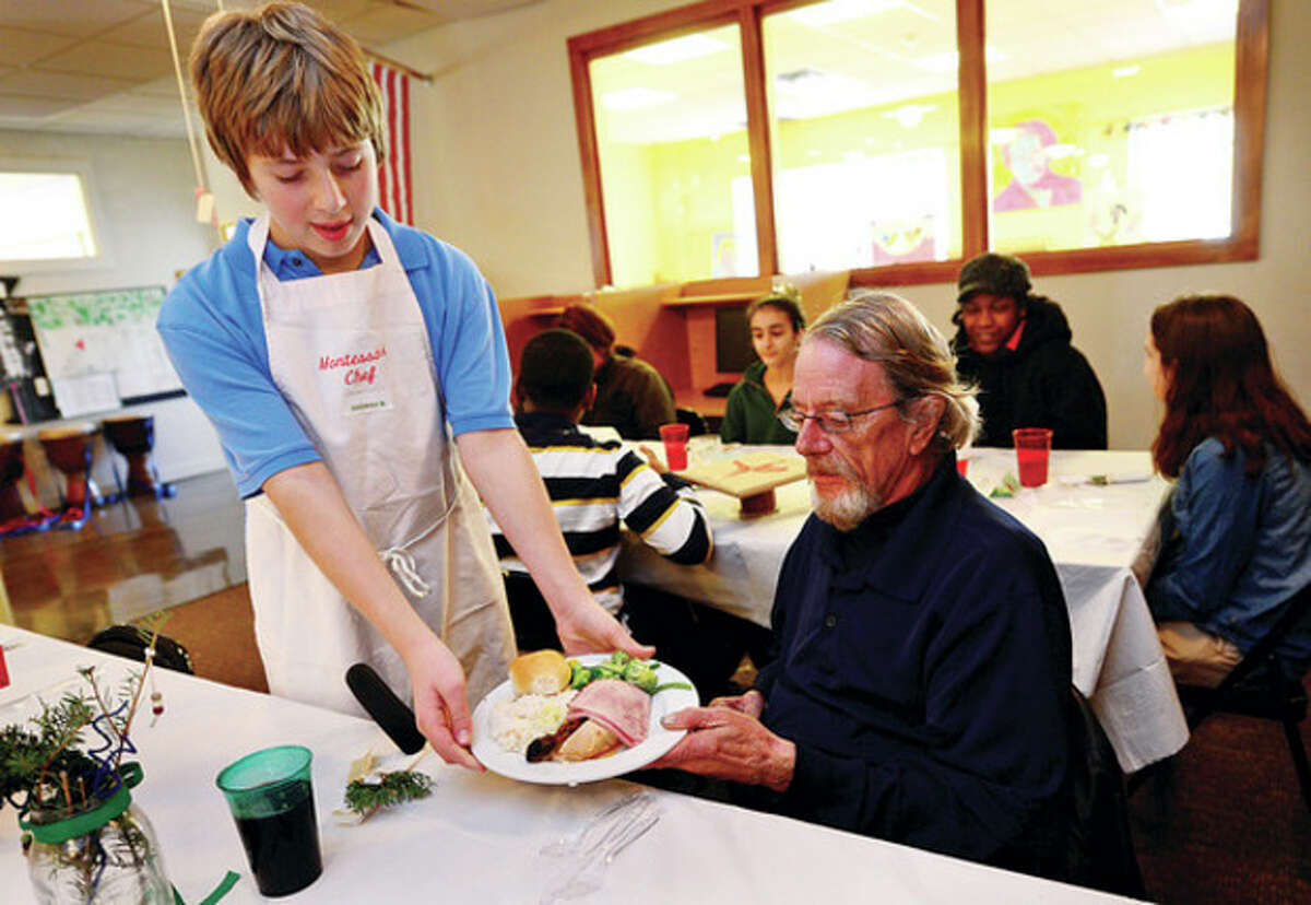 Hour photo / Erik Trautmann Montessori School student Thomas Bogaev serves up a holiday dinner to Open Door resident Thomas Bell Thursday as the school hosts the annual dinner where the students cook, serve and socialize for their guests from the Open Door Shelter.