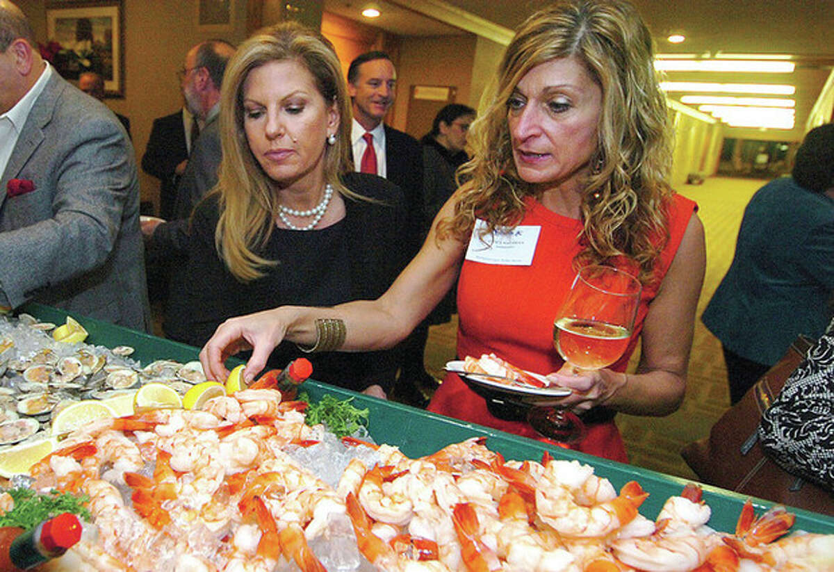 Hour Photo/Alex von Kleydorff. Eleni Sotiriou and Janet Nazaran sample the raw bar at the Chambers holiday dinner at Dolce