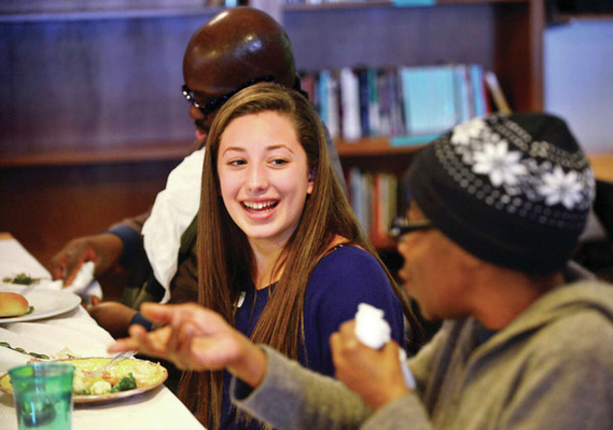 Montressori School student Gaby Pisano chats with Open Door resident Susie Hardy-Spencer Thursday as the school hosts the annual dinner where the students cook, serve and socialize with guests from the Open Door Shelter. Hour photo / Erik Trautmann