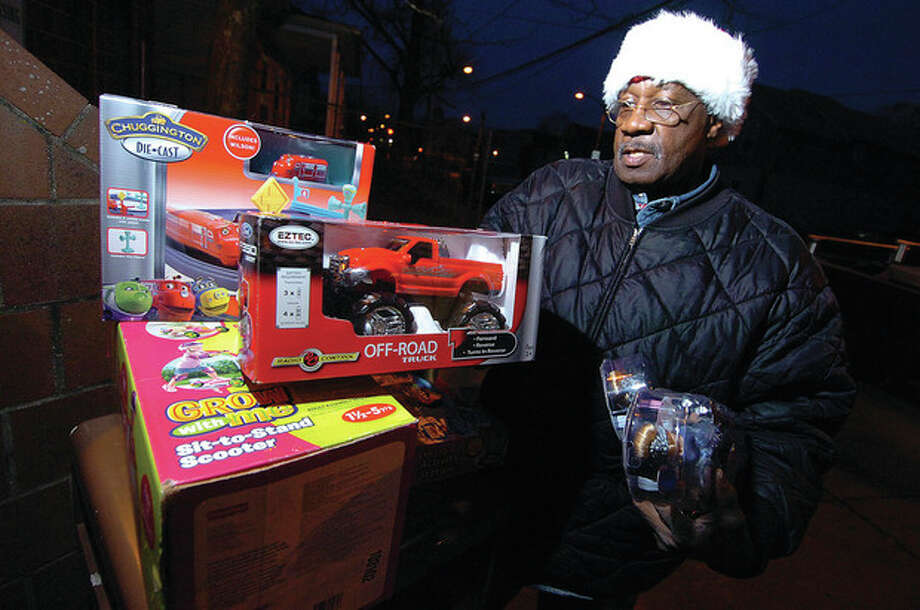 Hour photo / Alex von KleydorffErnie Dumas with some of the gifts he will pass out to children on Christmas Eve. / 2012 The Hour Newspapers/Alex von Kleydorff