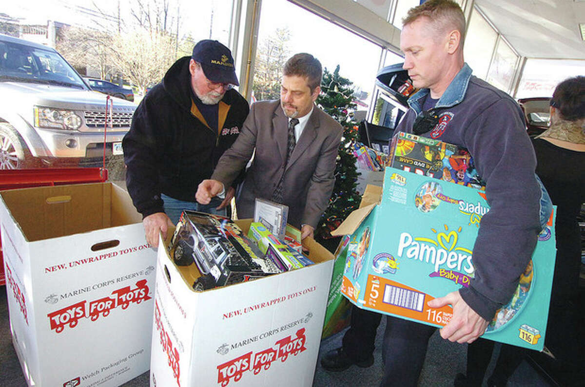Hour Photo/Alex von Kleydorff. l-r Marine Corps Toys for Tots Coordinator Peter Havens helps Al Alper and Wilton Firefighetr Jim Blanchfield to move some of the collected toys from Wilton Motors