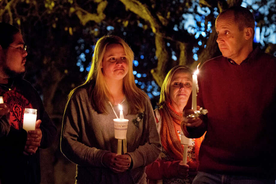 Kerin Sovern, center, who is from Sandy Hook, Connecticut, but now lives in San Diego, attends a candlelight vigil honoring victims of the Sandy Hook Elementary School in Connecticut at Balboa Park Thursday Dec. 20, 2012 with her parents Maureen and Michael Sovern who are visiting her from Sandy Hook. (AP Photo/U-T San Diego, Bill Wechter / UT San Diego