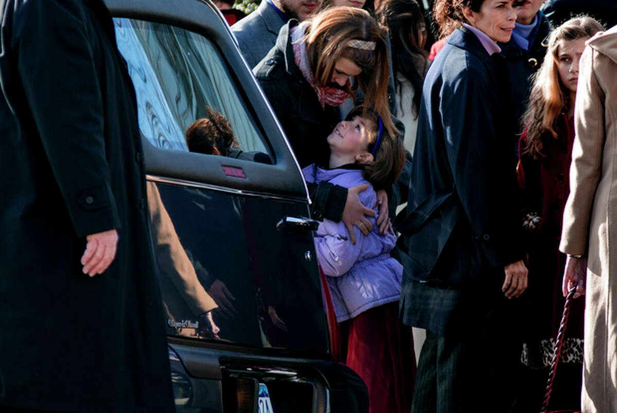 A child is embraced near a hearse carrying teacher Anne Marie Murphy, who was killed at the Sandy Hook Elementary School shootings in Newtown, after a funeral at St. Mary Of The Assumption Church in Katonah, N.Y. Thursday, Dec. 20, 2012. Newtown was killed when Adam Lanza, walked into Sandy Hook Elementary School in Newtown, Conn., Dec. 14, and opened fire, killing 26, including 20 children, before killing himself. (AP Photo/Craig Ruttle)