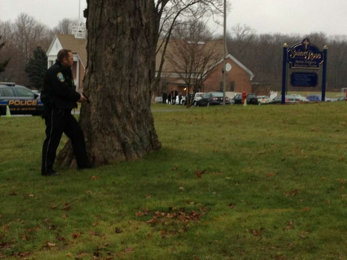 A local police officer can be seen here with his gun drawn in front of St. Rose Church in Newtown.