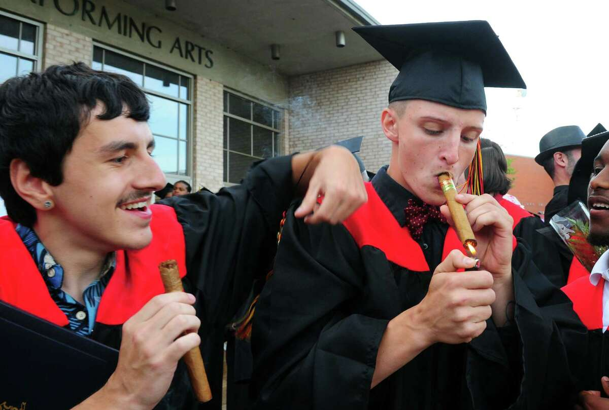Jeffrey Schilling, of Bridgeport, lights up a cigar to celebrate as his classmate Matt Correia, of West Haven, look on after Platt Technical High School's Class of 2016 Graduation held at Lyman Auditorium at Southern Connecticut State University in New Haven, Conn., on Wednesday June 15, 2016.