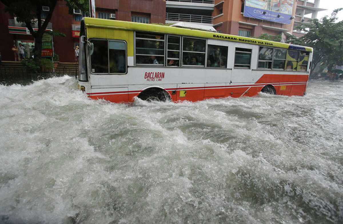 A bus barrels through flooded streets at the financial district of Makati, south of Manila, Philippines on Tuesday, Aug. 20, 2013. Flooding caused by some of the Philippines' heaviest rains on record submerged more than half the capital Tuesday, turning roads into rivers and trapping tens of thousands of people in homes and shelters. The government suspended all work except rescues and disaster response for a second day. (AP Photo/Aaron Favila)