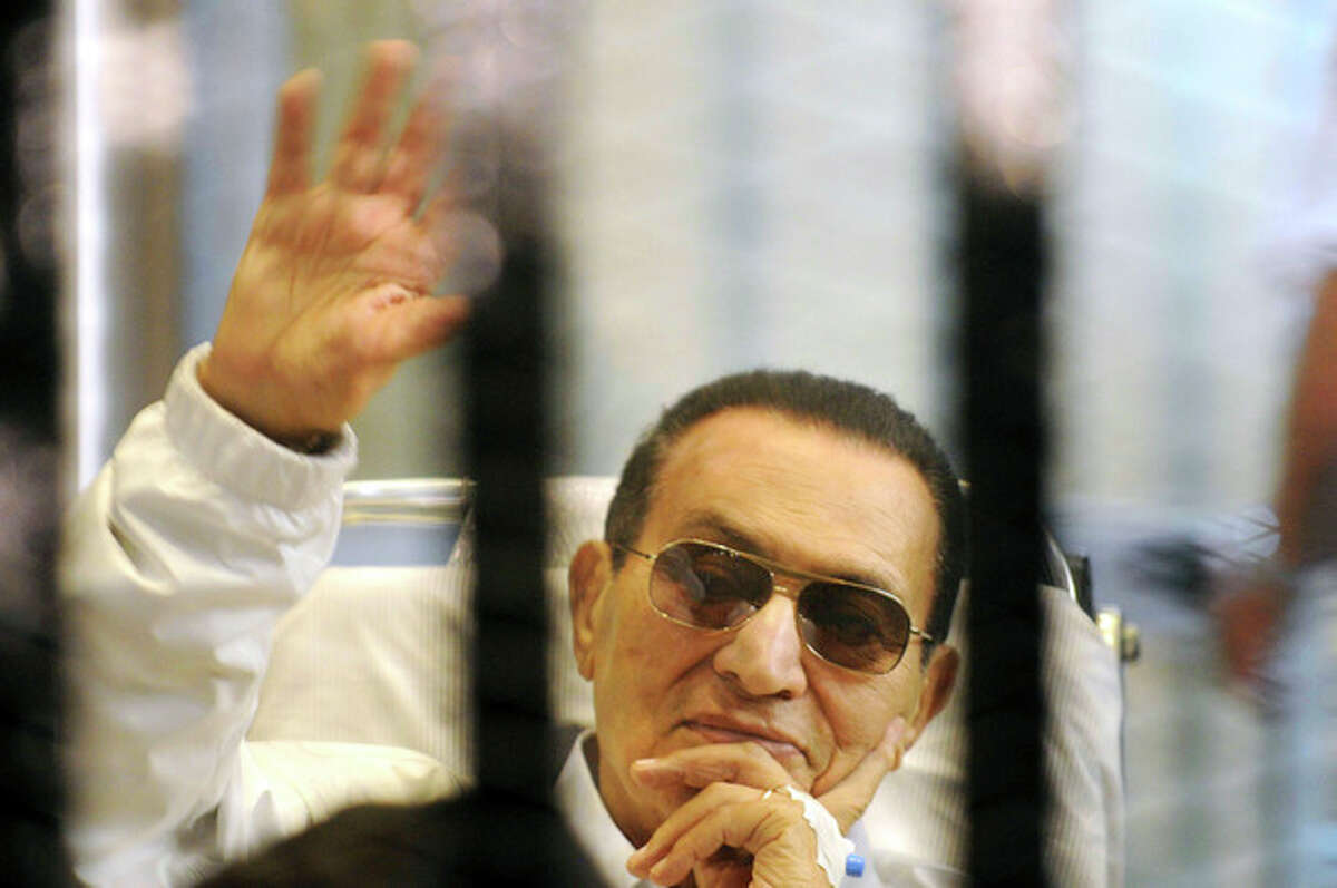 FILE -- In this Saturday, April 13, 2013 file photo, former Egyptian President Hosni Mubarak waves to his supporters from behind bars as he attends a hearing in his retrial on appeal in Cairo, Egypt. Egyptian judiciary officials say former President Hosni Mubarak could be freed from custody this week. They say a court on Monday, Aug. 19, 2013 ordered his release in a corruption case that alleged he and his two sons embezzled funds for presidential palaces. (AP Photo, File)