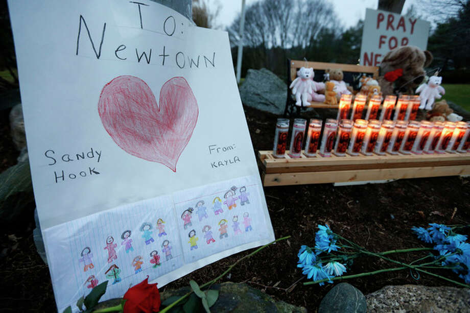 A child's message rests with a memorial for shooting victims, Sunday, Dec. 16, 2012, in Newtown, Conn. A gunman walked into Sandy Hook Elementary School in Newtown on Friday and opened fire, killing 26 people, including 20 children. (AP Photo/Jason DeCrow) / FR103966 AP