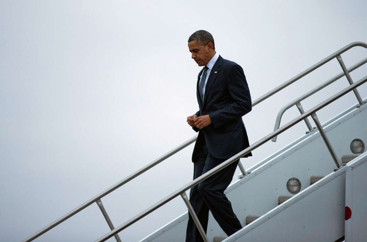President Barack Obama arrives at Bradley Air National Guard Base on Sunday, Dec. 16, 2012, in East Granby, Conn. He is scheduled to attend an interfaith vigil for the victims of Friday's Sandy Hook Elementary School shooting in Newtown, Conn., where a gunman killed 26 people, including 20 children. (AP Photo/ Evan Vucci)