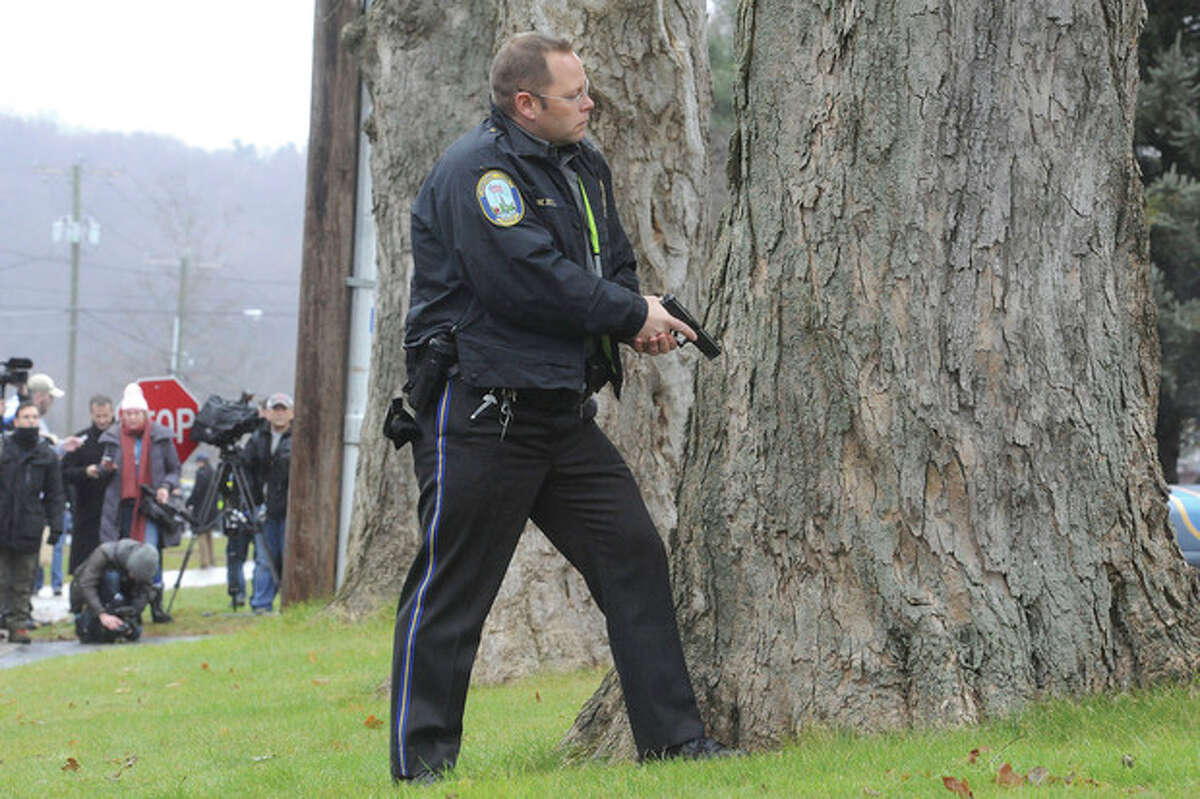 Hour photo/Matthew Vinci Above, police wait aside Saint Rose of Lima church in Newtown Sunday when a threat was called in during the service. At left, a mourner pays respects Sunday at Saint Rose of Lima church in Newtown, one of the many services for the victims of Sandy Hook Elementary school.