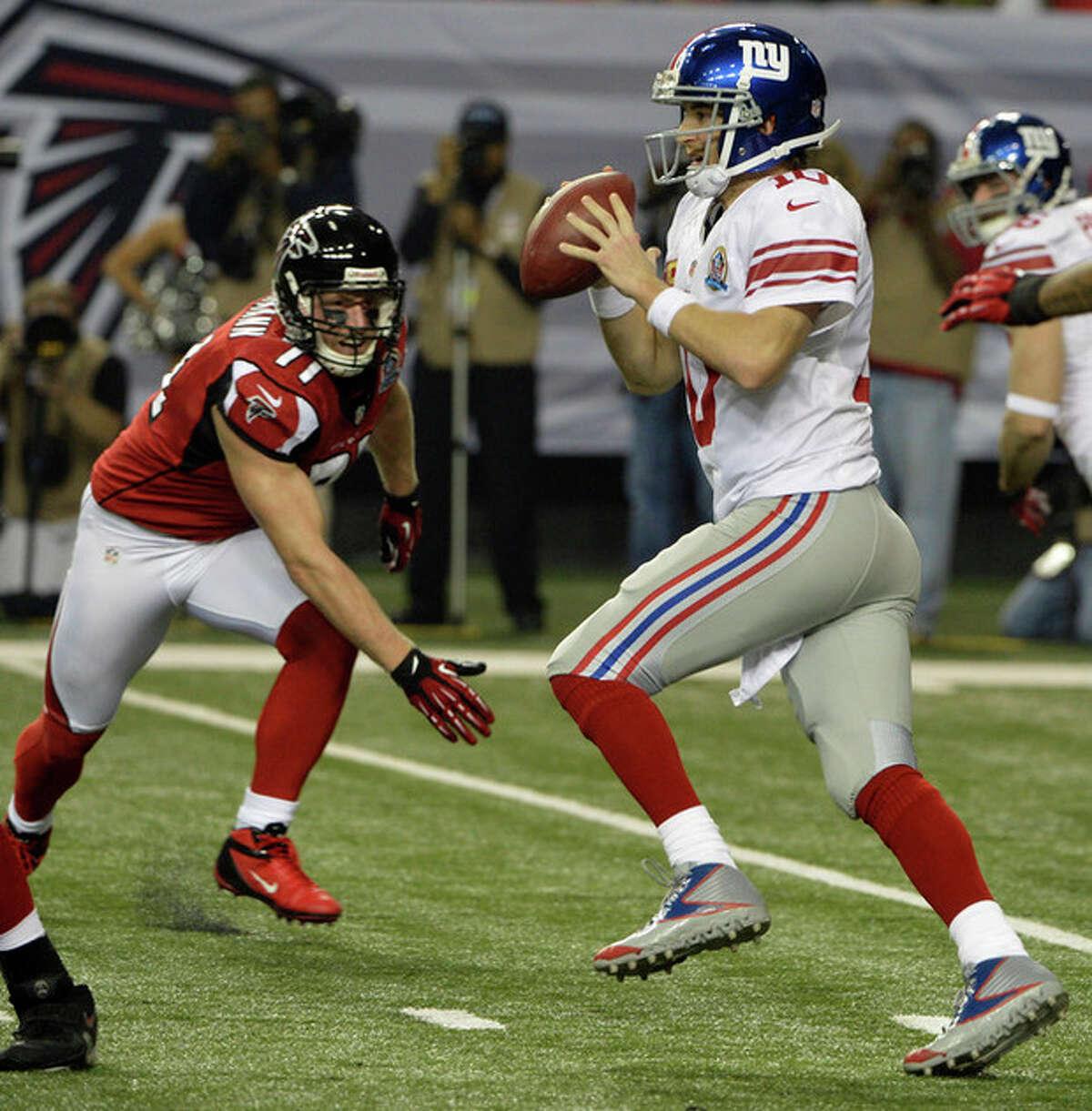 New York Giants quarterback Eli Manning (10) runs out of the pocket as Atlanta Falcons defensive end Kroy Biermann (71) pursues during the first half of an NFL football game, Sunday, Dec. 16, 2012, in Atlanta. (AP Photo/Rich Addicks)