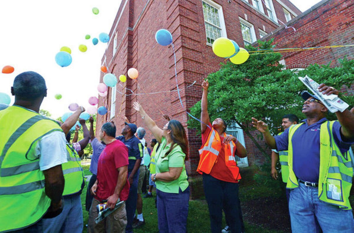 The First Student bus company and the Norwalk Public Schools Transportation Office honor the late Jesse Montgomery, a long-time, well-loved bus driver for the Norwalk schools by retiring his bus number and releasing balloons following the company's Start Up meeting Tuesday morning at City Hall. Hour photo / Erik Trautmann