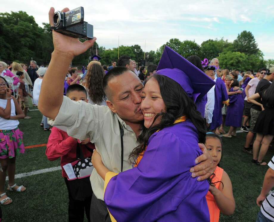 Angel Uchupailla kisses his daughter Katherine Martinez following the Westhill High School Class of 2016 commencement at the school in Stamford, Conn., on Wednesday, June 15, 2016. Photo: Matthew Brown, Hearst Connecticut Media / Stamford Advocate