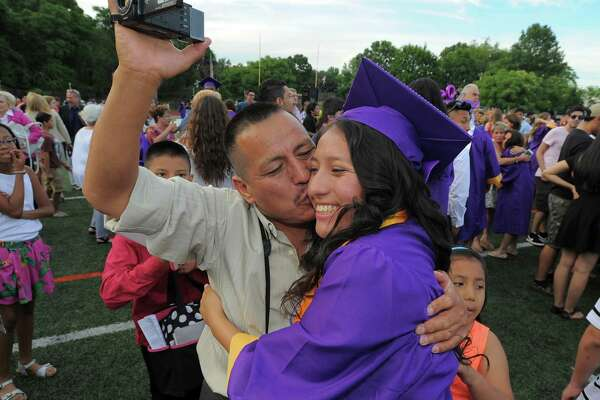 Angel Uchupailla kisses his daughter Katherine Martinez following the Westhill High School Class of 2016 commencement at the school in Stamford, Conn., on Wednesday, June 15, 2016.