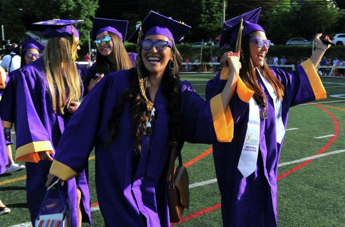 Nancy Juarez and Ariana Venneri cheer along with classmates as they march in the processional during Westhill High School Class of 2016 commencement at the school in Stamford, Conn., on Wednesday, June 15, 2016.
