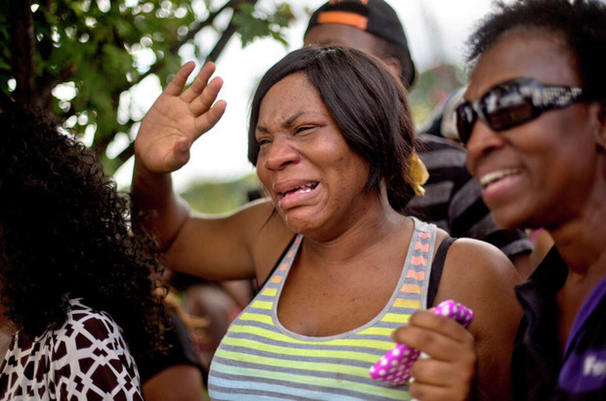 Sparkle Potts, left, cries upon seeing her nephew Cameron Bell pull up in a school bus from Ronald E. McNair Discovery Learning Academy while waiting with his grandmother Arvis Potts, right, in a Wal-Mart Inc., parking lot after students were evacuated when a gunman entered the school, Tuesday, Aug. 20, 2013, in Decatur, Ga. (AP Photo/David Goldman)