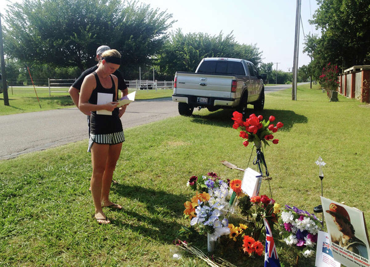 Sarah Harper,Christopher Lane's girlfriend, stands beside a memorial along the road where police say Lane, an Australian baseball player was shot and killed Friday, Aug. 16, 2013 by three ?