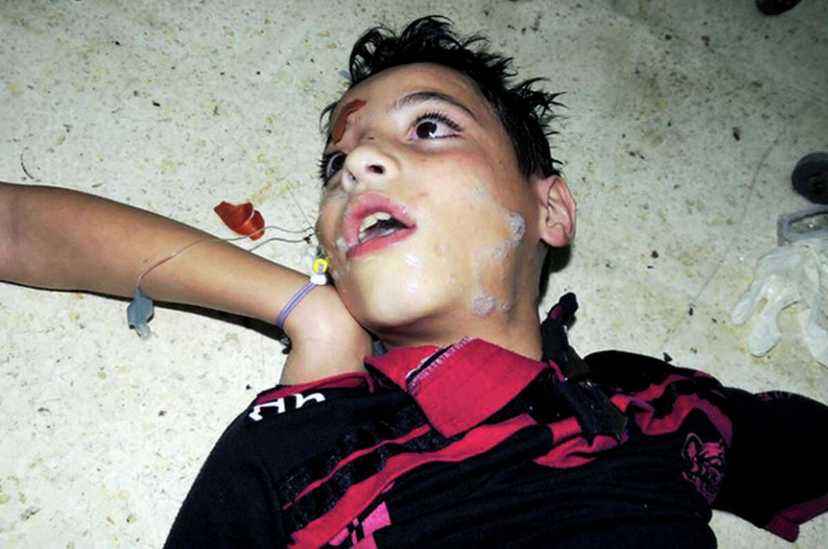 This citizen journalism image provided by the Local Committee of Arbeen which has been authenticated based on its contents and other AP reporting, shows a Syrian boys waiting to receive treatment at a makeshift hospital, in Arbeen town, Damascus, Syria, Wednesday, Aug. 21, 2013. Syrian regime forces fired intense artillery and rocket barrages Wednesday on the eastern suburbs of the capital Damascus, in what two pro-opposition groups claimed was a